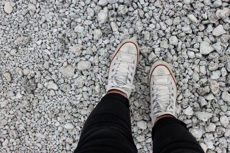 Fötter med vita converse mot grus.
