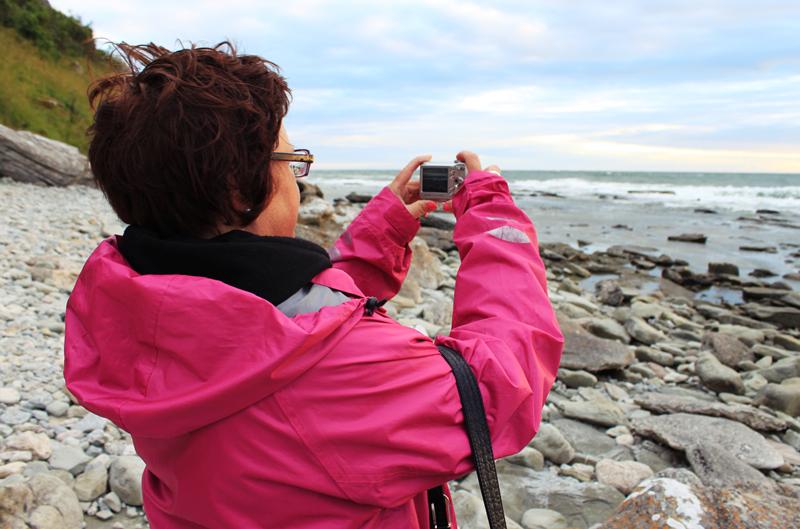 Person fotograferar havet med digitalkamera.