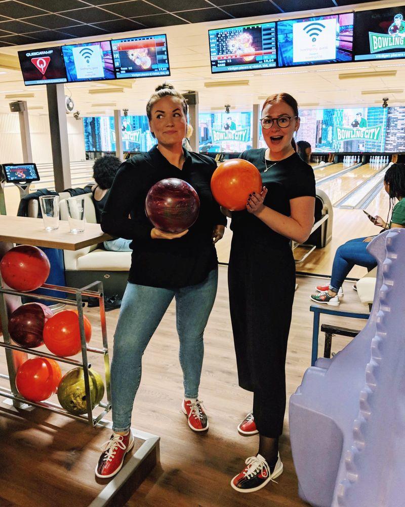 Två personer håller varsitt bowlingklot i en bowlinghall.