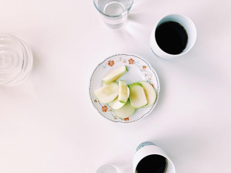 En assiett med skivat äpple på. På bordet står också två koppar kaffe.