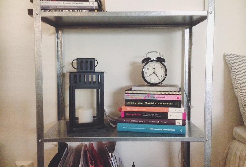 En ljuslykta, en klocka och en trave böcker i en hylla.