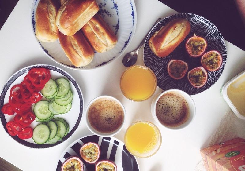 Ett bord med frukost - kaffe, apelsinjuice, baguetter, frukt och grönsaker.
