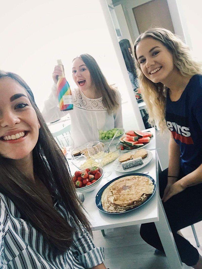 Tre kvinnor ler vid ett bord där det finns pannkakor och cava.
