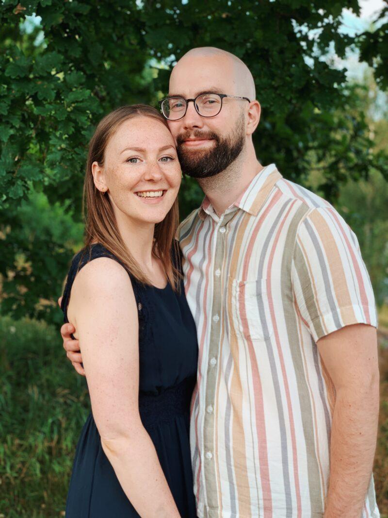 Ett par håller om varandra och ler mot kameran.
