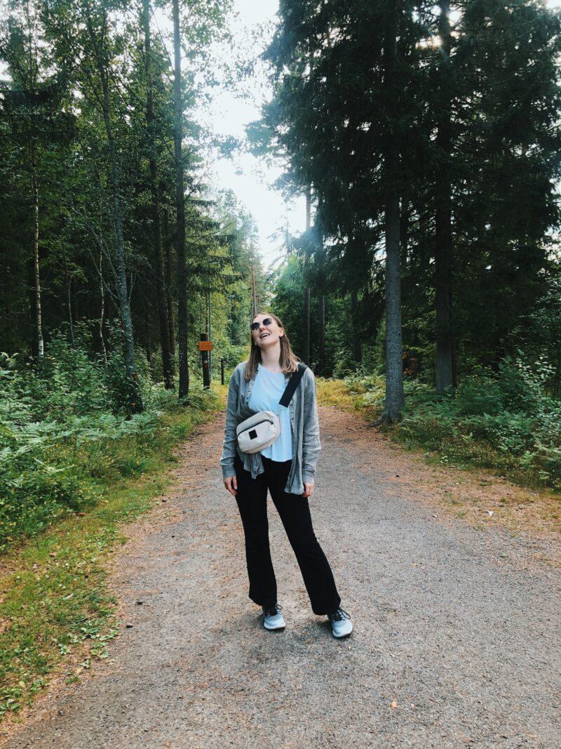 En kvinna står på en skogsväg och tittar upp mot himlen.