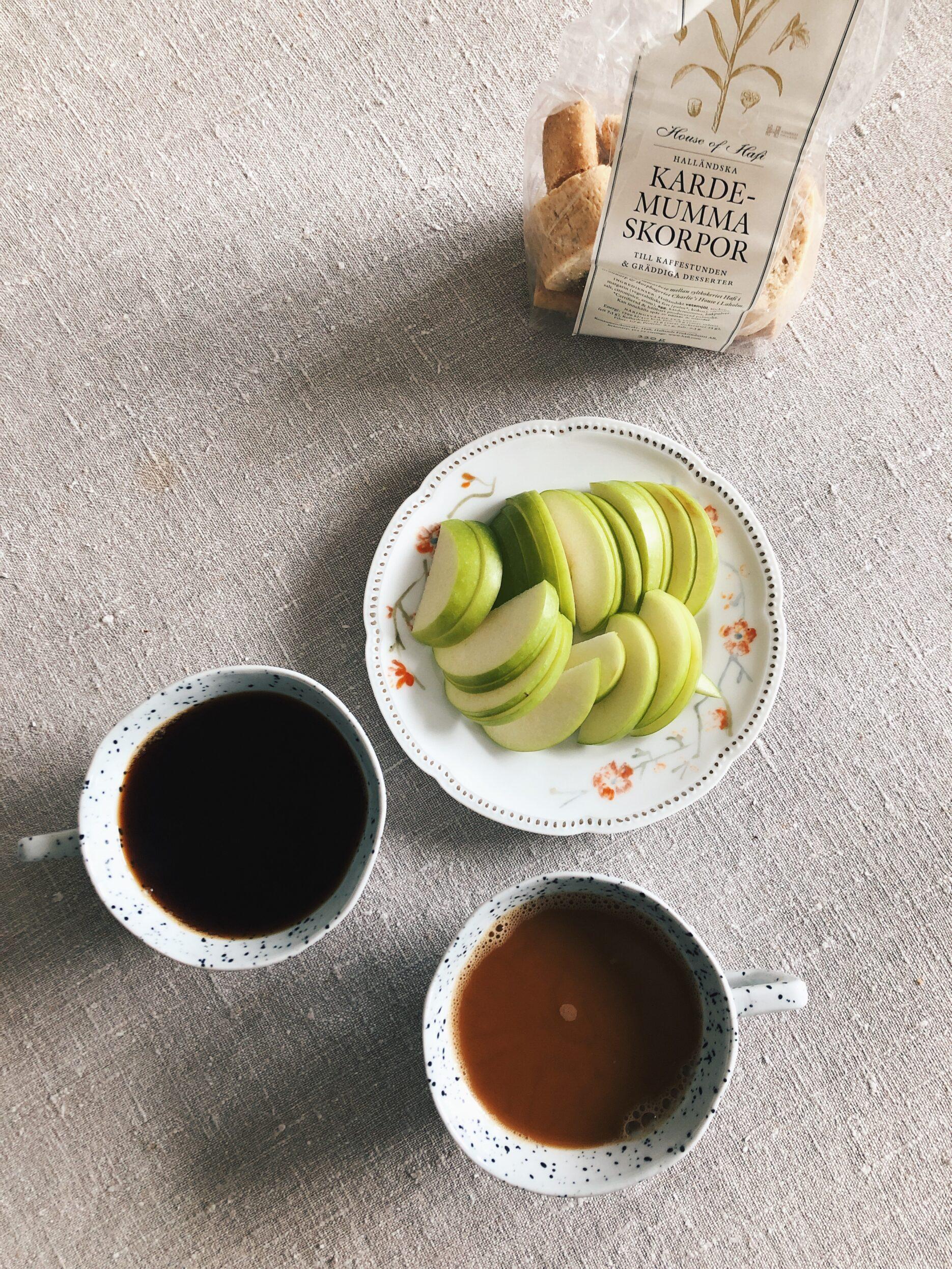 Två kaffekoppar, uppskuret grönt äpple och kardemumma skorpor.
