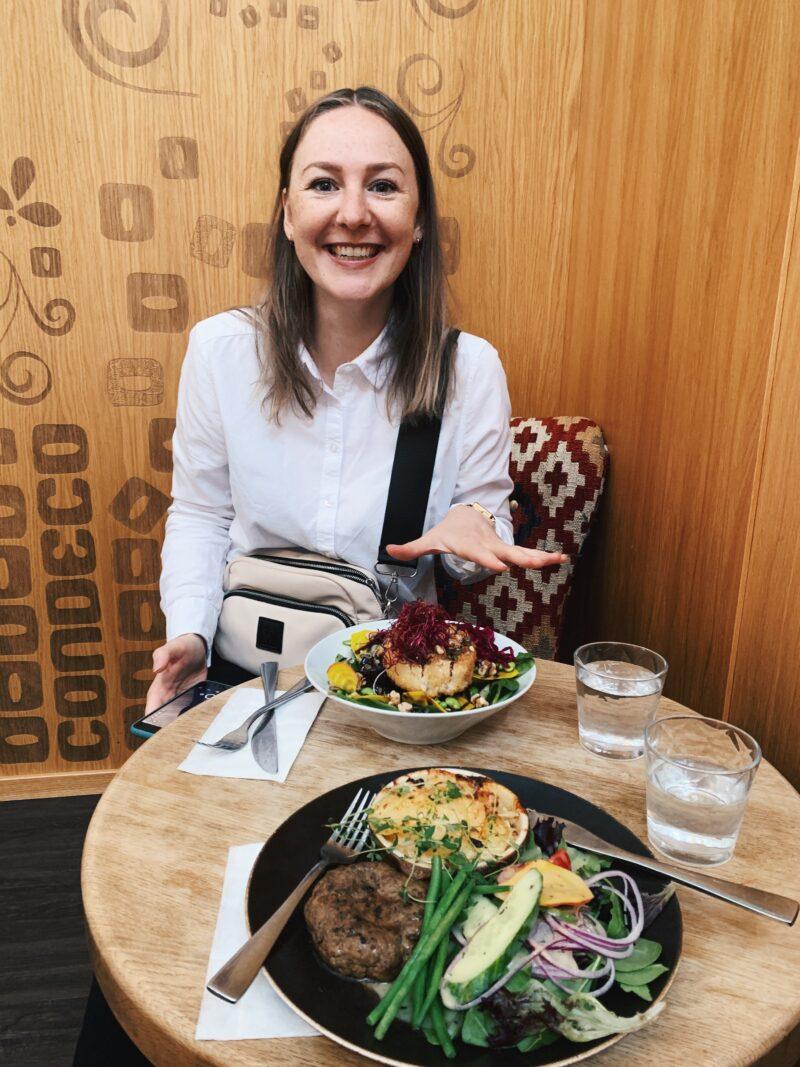 En glad kvinna sitter vid ett bord och äter lunch.