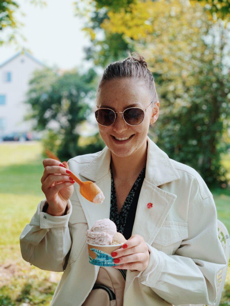 Kvinna med solglasögon äter glass med sked.